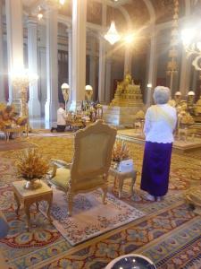 Sa Majesté la Reine-Mère recueillie pendant que Sa Majesté le Roi allume les baguettes d'encens de l'autel royal